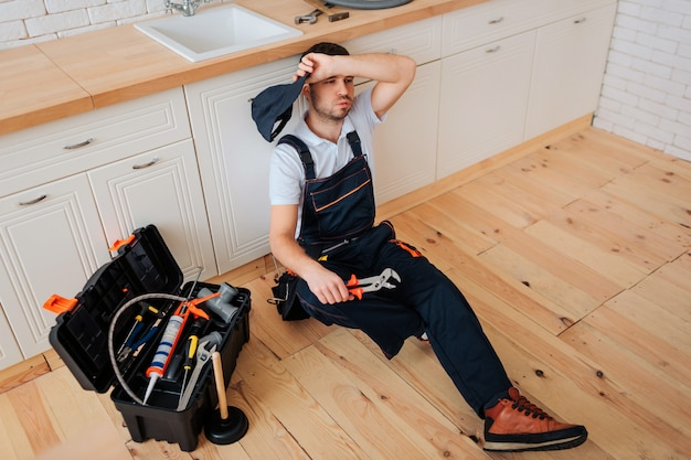 Tired exhausted plumber sit on floor in kitchen