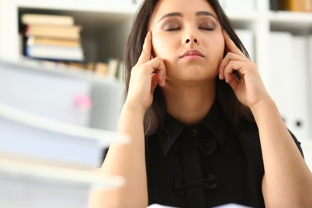 Tired and exhausted woman looks at documents propping up her head with her hands