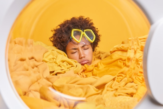 피곤한 젊은 여성 가사도우미는 세탁기에서 더러운 옷으로 둘러싸인 스노클링 마스크를 쓰고 집에서 빨래를 하느라 바쁜 표정을 짓고 있다