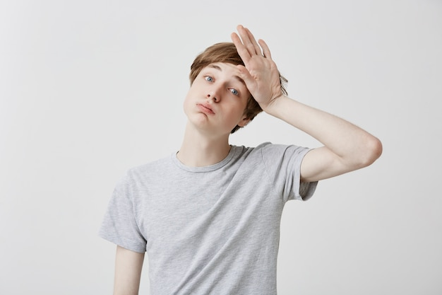 Tired fair-haired young man feels headahce after hard work, touches head with hand, stressed. regretful caucasian guy has forgetful expression, tries to remember all necessary details