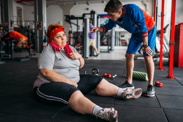 Tired fat woman sits on the floor, workout with instructor in gym. calories burning, obese female person in sport club