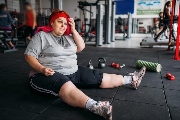疲れた太った女性がジムの床に座っています。カロリー燃焼、スポーツクラブの肥満女性