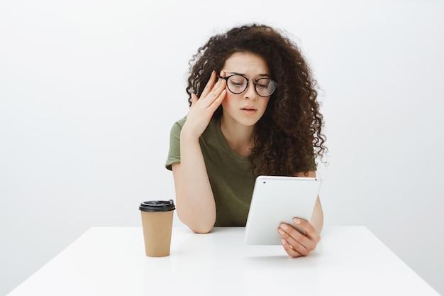 Усталая сытая подруга с кудрявыми волосами сидит за столиком в кафе, пьет чай или кофе и читает статью на цифровом планшете, держась за висок