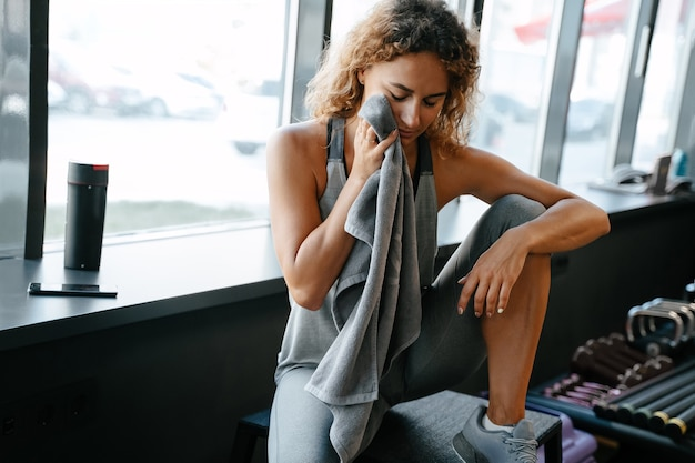 활발한 신체 운동 후 피곤한 여성 운동 선수는 체육관 개념에서 수건으로 땀을 닦고 있습니다...