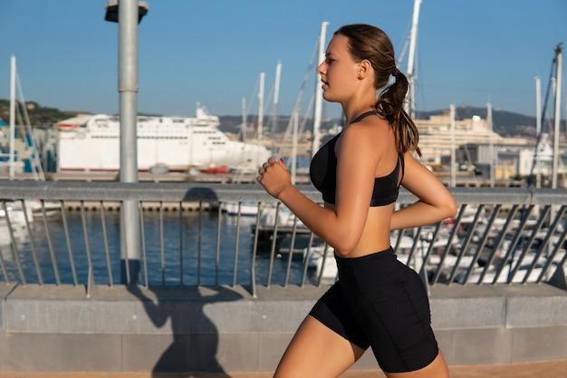 港の近くでジョギングしている疲れた女性アスリート
