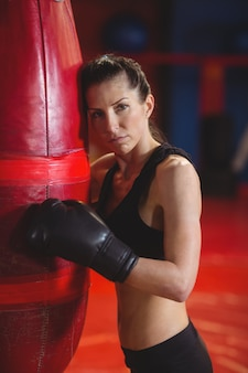Tired female boxer leaning on punching bag