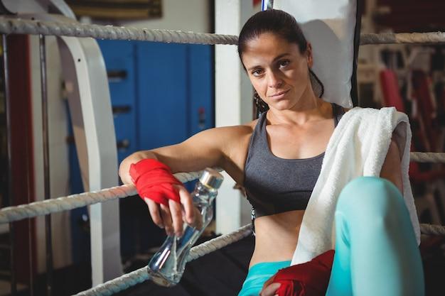 リングに座って疲れている女性ボクサー