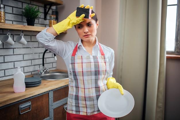 疲れた女性クリーナーはキッチンに立ち、額に手を握る。彼女はエプロンと黄色の手袋を着用します。女性は白いプレートを保持します。