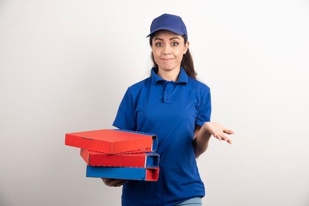 Corriere femminile stanco con cartone di pizza e appunti