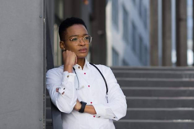 クリニックで忙しい一日を過ごした後の疲れた女性医師、激しい頭痛と過労後のうつ病を伴うクリニックでのアフリカ系アメリカ人の女性