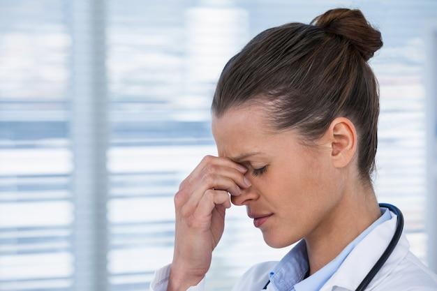 頭痛を持っている疲れている女性医師