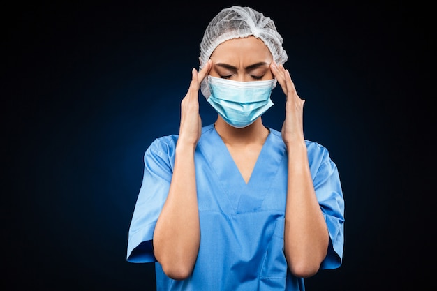 Tired female doctor in medical mask and cap has a headache isolated