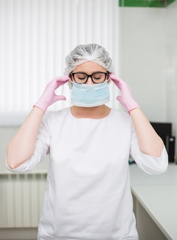 Tired female doctor wearing glasses and a white uniform puts on a disposable protective mask in the clinic office