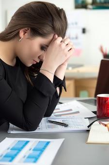 Усталая сотрудница на рабочем месте в офисе, касаясь ее головы. сонный работник рано утром после ночной работы. понятие переутомления, ошибки, стресса, увольнения или депрессии