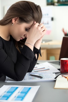 Tired female employee at workplace in office touching her head. sleepy worker early in the morning after late night work. overworking, making mistake, stress, termination or depression concept