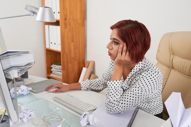 しわくちゃの紙と文書の断片とテーブルでコンピューターに取り組んでいる疲れた女性マネージャー