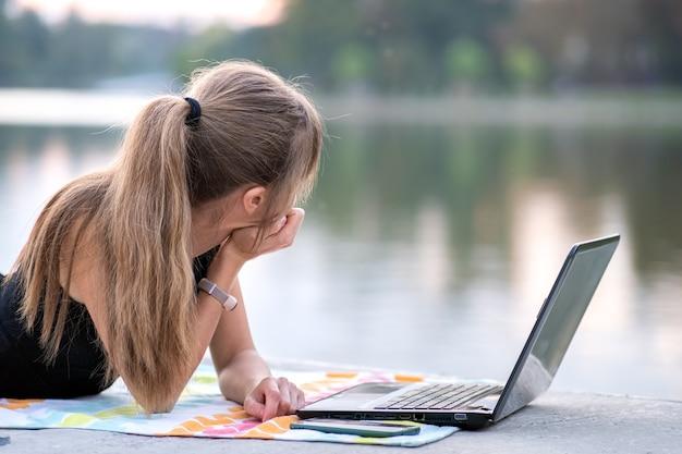 Усталый женский офисный служащий, работающий за портативным компьютером, лежа в летнем парке на открытом воздухе.