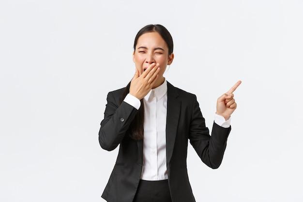 Усталая женщина-офис-менеджер, предприниматель в костюме, указывая пальцем вправо и зевая. скучающая или измученная азиатская бизнес-леди работает допоздна, показывая проект, стоя на белом фоне