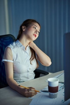 Усталая женщина-менеджер проектов потирает затекшую шею после целого дня работы за столом