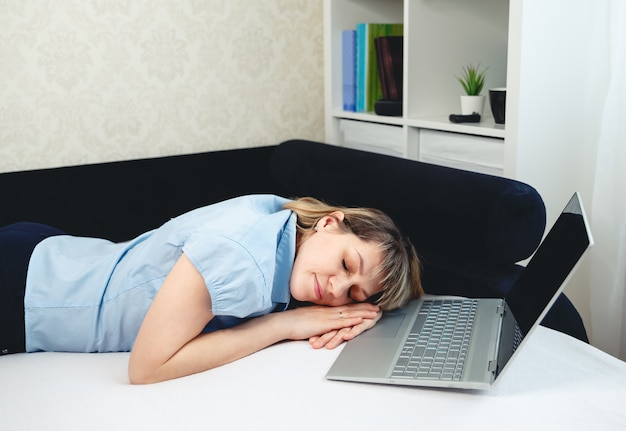 Tired female sleeping. sleepy girl working remotely in front of laptop