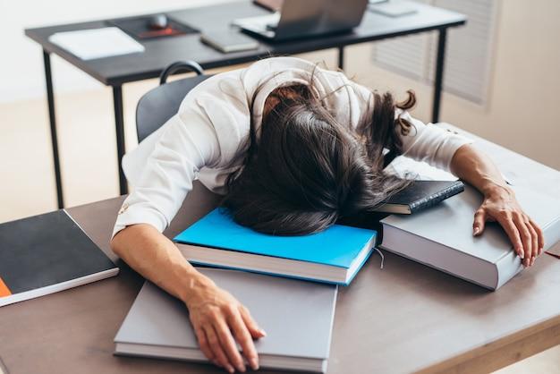 Tired female teacher sleeping on desk face and hands on books.