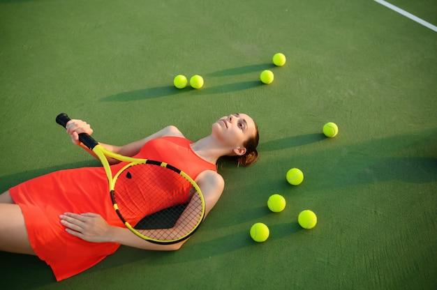 ラケットで疲れた女性テニスプレーヤーは、屋外コートに横たわっています。アクティブで健康的なライフスタイル、スポーツゲームの競争、ラケットを使ったハードフィットネストレーニング