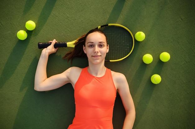 ラケットで疲れた女性テニスプレーヤーは、屋外コートに横たわっています。アクティブで健康的なライフスタイル、スポーツゲームの競争、ハードフィットネストレーニング