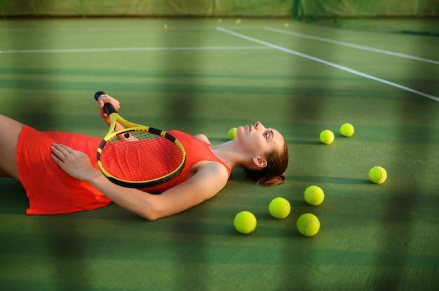 ラケットで疲れた女性テニスプレーヤーは屋外コートに横たわっています