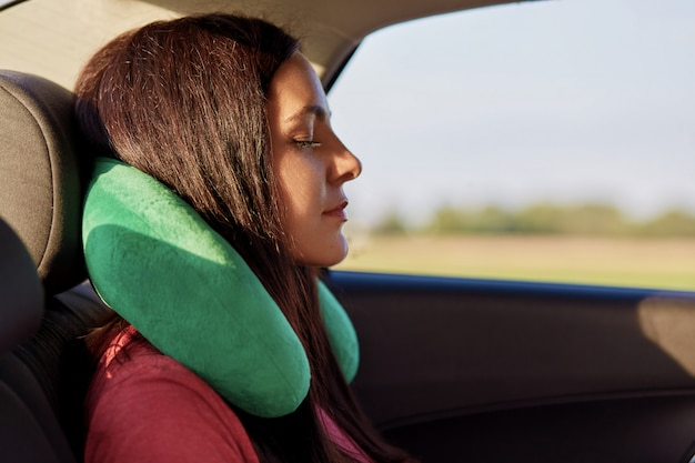 Tired female traveller uses travel pillow, sleeps in car, covers long distance