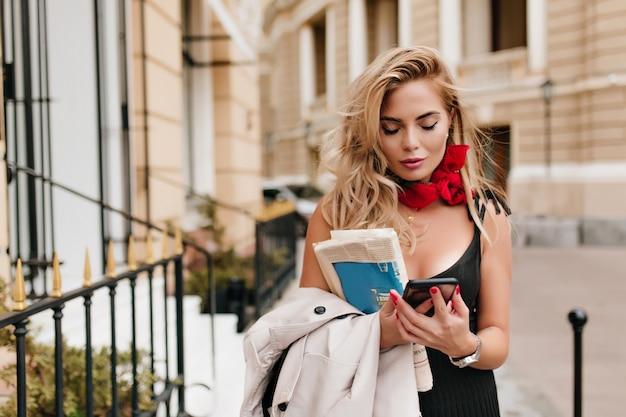 Donna femmina stanca con pelle abbronzata utilizza lo smartphone mentre aspetta qualcuno per strada
