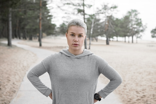 야외에서 포즈를 취하는 까마귀에 피곤한 맞는 슬림 소녀, 그녀의 허리에 손을 유지하고 카메라를보고, 심장 달리기 운동 중 휴식을 취하십시오. 사람, 라이프 스타일, 활동, 건강 및 피트니스 개념