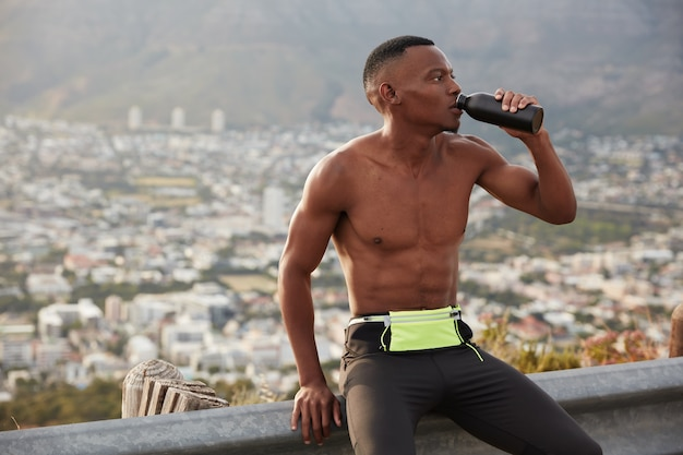 Tired fitness dark skinned athletic person drinks water, prevents himself from dehydration, holds sport bottle, fatigue after sport summer exercise, leads active healthy lifestyle, sits at road sign