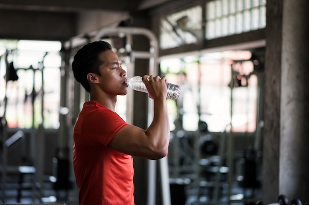 Tired fitness man drink water in gym