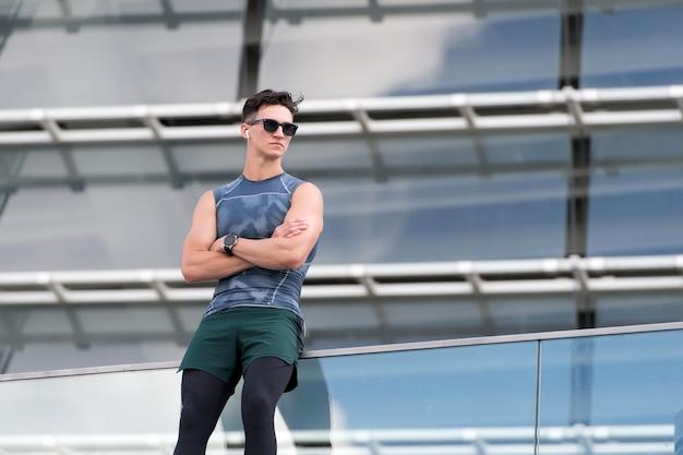 Усталый фитнес-мужчина, отдыхающий, слушая музыку, оставаясь в форме и здоровой спортивной жизни молодой мужчина