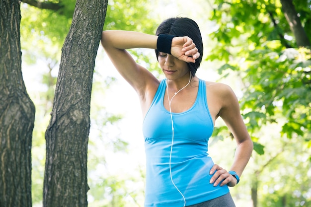 Tired fitness woman resting outdoors