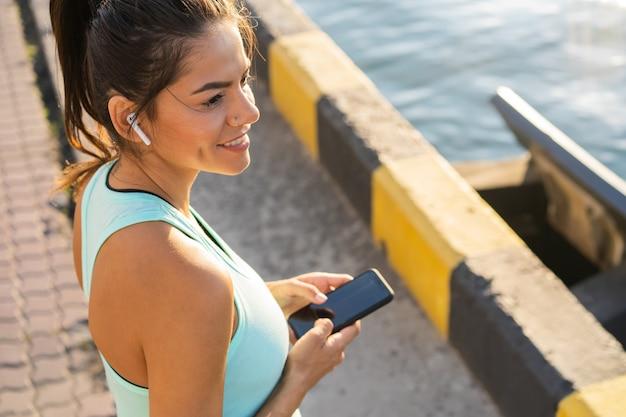 Усталая женщина фитнеса потеет, принимая перерыв, слушая музыку на телефоне после трудной тренировки. молодая женщина слушает музыку в наушниках в приложении для смартфона для фитнес-мотивации