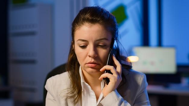 夜遅くに営業所で残業して疲れ果てて仕事をしながら電話で会話をしている疲れたフリーランサーの女性。最新のテクノロジーネットワークワイヤレス過労を使用して集中している従業員