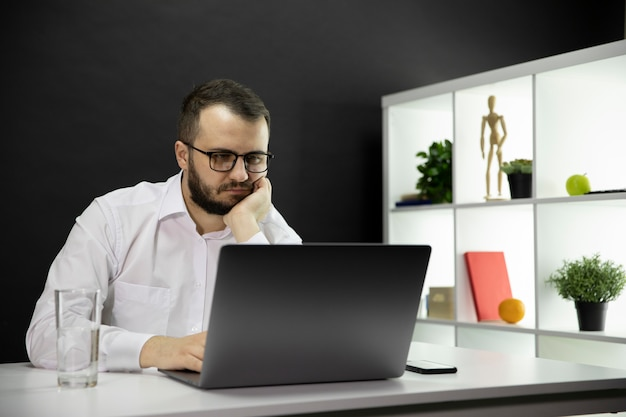 Tired freelancer working at computer in home office, emotional, physical burnout