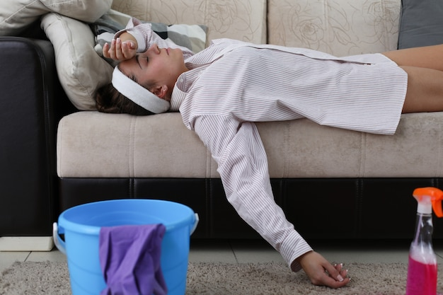 Tired from cleaning girl lies at home on couch