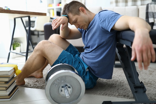 Tired from sports exercises guy sits floor at home