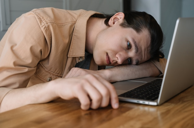 Tired and frustrated business man sleeping at laptop