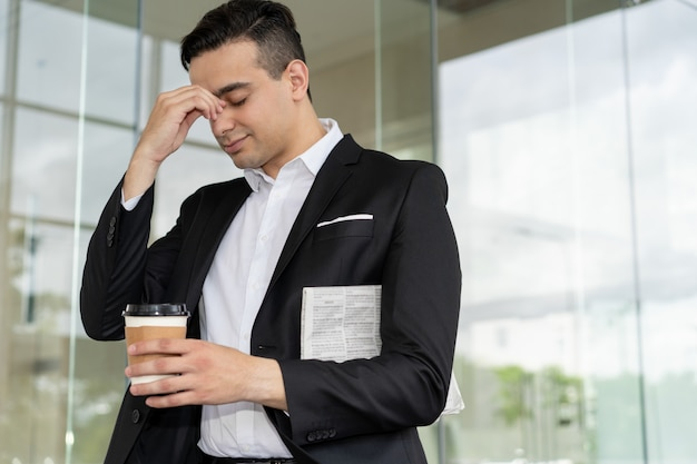 Tired frustrated businessman suffering from headache