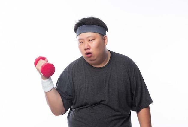 Утомленный смешной тучный азиатский человек в костюмах спортов работая с гантелью и смотря к камере изолированной на белой предпосылке