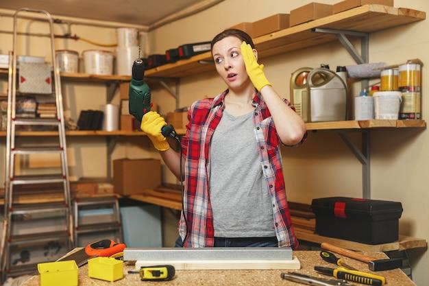 Усталая гага кавказская молодая женщина с каштановыми волосами в клетчатой рубашке и серой футболке работает в столярной мастерской за столом, сверлит просверленные отверстия в куске железа и дерева при изготовлении мебели.