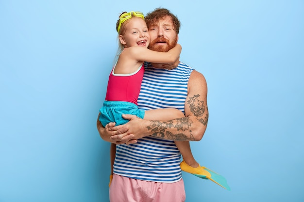 Tired ginger father and daughter posing in pool outfits