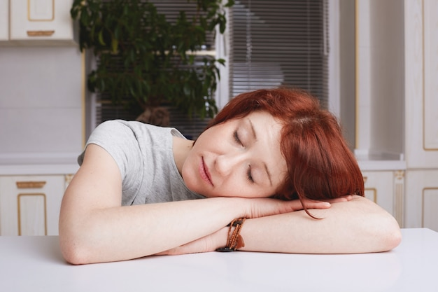 Tired ginger housewife takes nap, leans head on hands