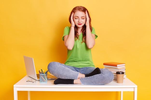 疲れた生姜若い女性は頭に触れる従業員を疲れさせた