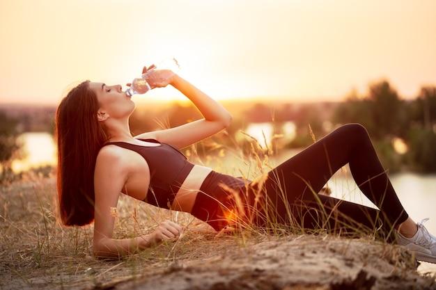 疲れた女の子アスリートは、日没時に湖に横たわっている間、ボトルから水を飲みます