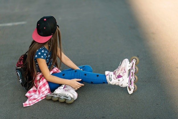 Tired girl in a cap and roller skates resting sitting on the road.