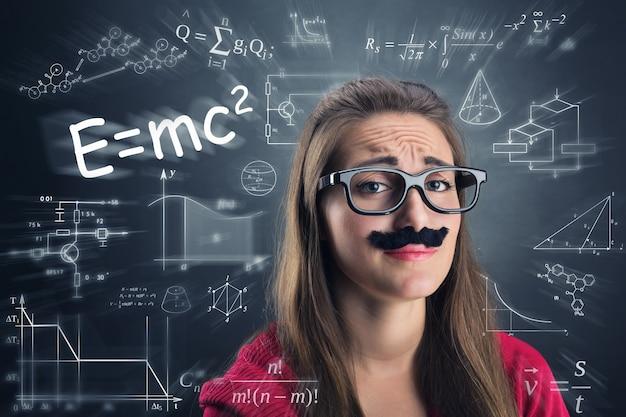 疲れた女の子は、数式で科学の背景の上に眼鏡と偽の口ひげを身に着けています